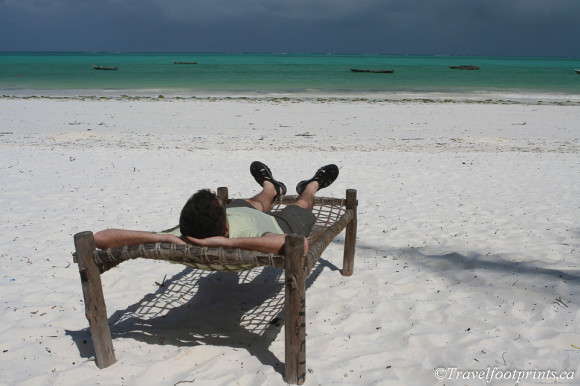 man relaxing in lounge chair on paje beach zanzibar