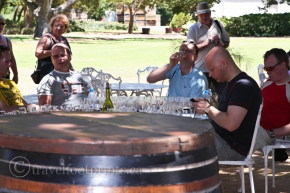 Men-sitting-drinking-wine-Franschhoek-South-Africa-Winelands-barrel-glasses