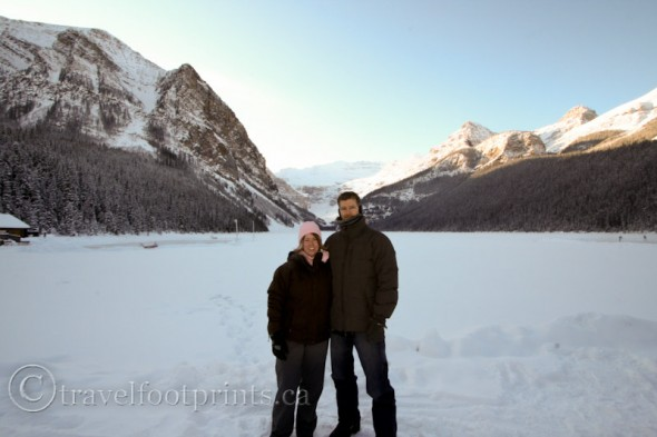 two-people-hats-standing-front-lake-louise-mount-victoria-glacier-snow