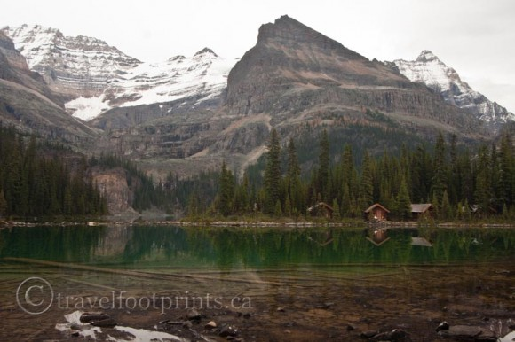 lake-ohara-mountain-view-cabins-green-water-snow-capped