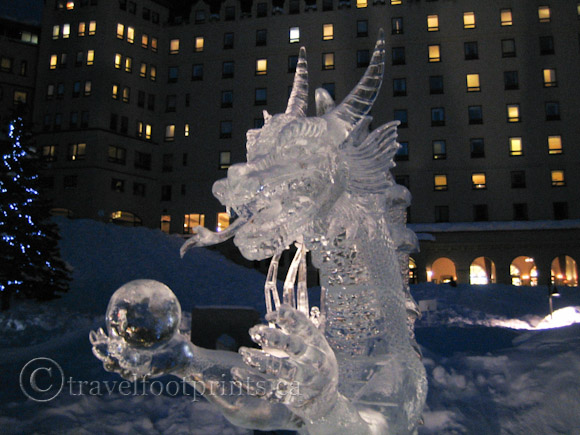 lake-louise-ice-magic-festival-night-dragon-holding-ball-sculpture-fairmont