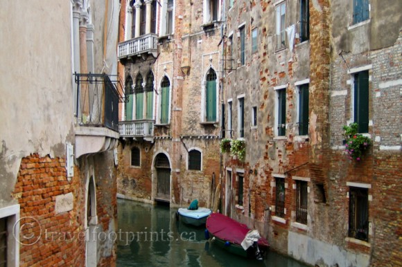 very-narrow-canal-venice-italy-boat-tall-building-balcony-window