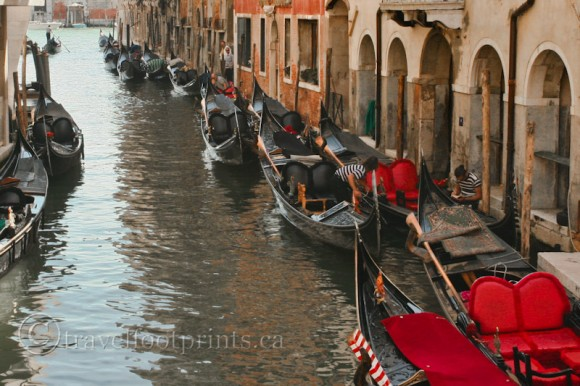 row-gondolas-narrow-venice-canal-red-seats-italy