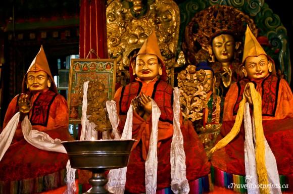 gold-religious-statues-sera-monastery-lhasa-tibet-red-robes-white-scarves
