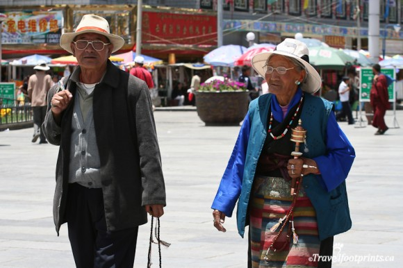 old-tibetan-couple-walking-lhasa-johkang-prayer-wheel-eye-glasses-hats