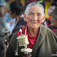 elderly tibetan lady holding prayer wheel