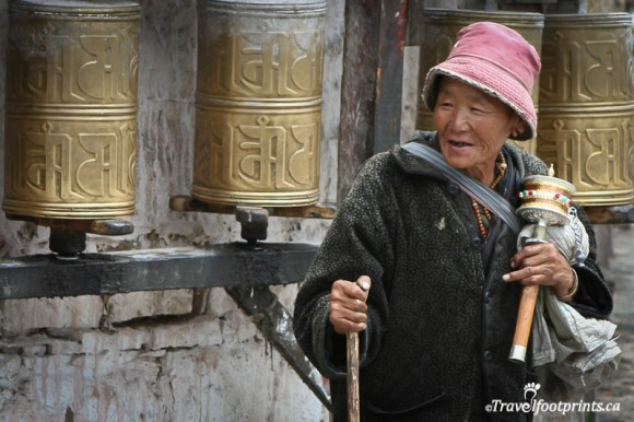 elderly-tibetan-lady-in-front-of-large-prayer-wheels-wearing-pink-hat