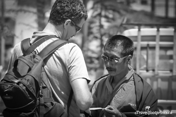 caucasian-man-wearing-backpack-talking-to-tibetan-monk-with-sunglasses-lhasa
