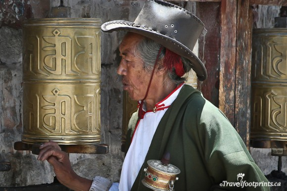 tibetan-man-wearing-green-cloak-leather-cowboy-hat-turning-large-prayer-wheel-lhasa