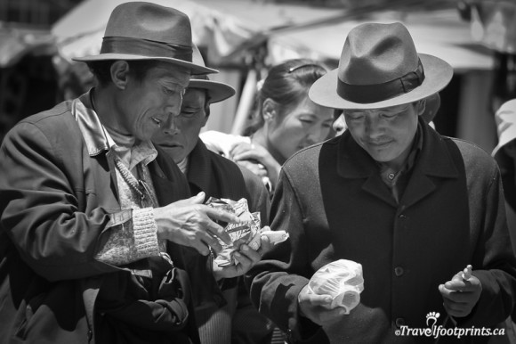 tibetan-men-wearing-hats-exchanging-packages-in-their-hands-lhasa