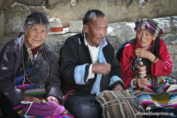 three-tibetan-people-in-traditional-clothing-sitting-in-front-of-alter-with-prayer-wheels-smiling-lhasa