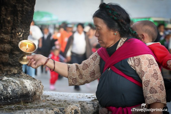 tibetan-lady-pouring-candle-wax-on-alter-baby-on-back-braided-hair-lhasa-johkang-religion