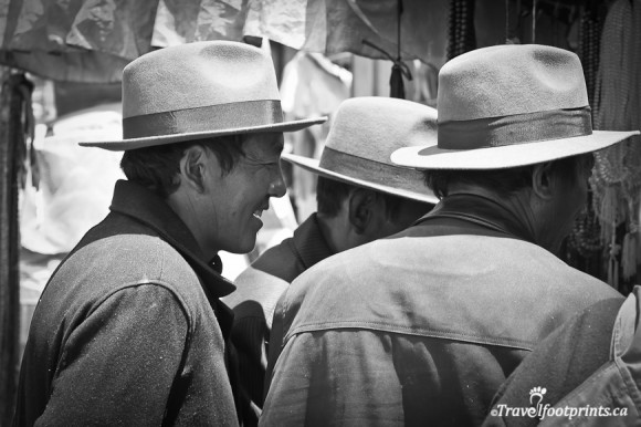 men-wearing-hats-smiling-looking-at-vendor-stalls-in-lhasa-tibet