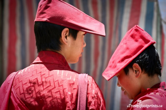 two-female-monks-with-red-hats-and-robes-pin-striped-background-lhasa-tibet