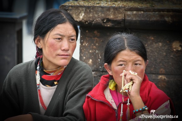 young-tibetan-ladies-holding-prayer-beads-black-robe-braided-hair-sitting-lhasa