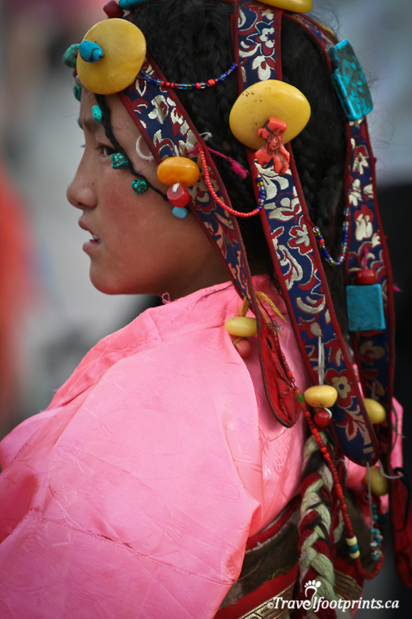 beautiful-young-tibetan-girl-wearing-traditional-clothing-pink-robe-beaded-head-dress-in-braided-hair-lhasa