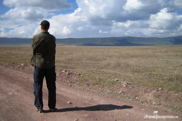 man-standing-hat-plains-ngorongoro-crater-mountains-cloudy-sky-dirt-road