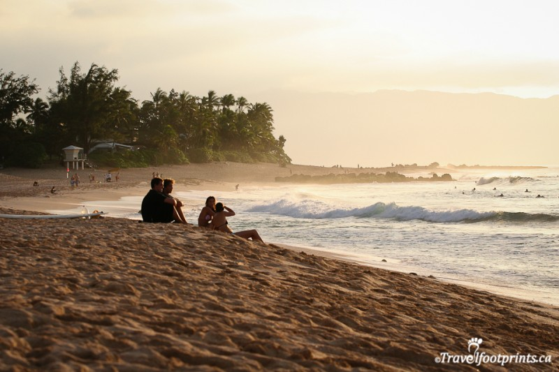 sandy-beach-north-shore-oahu-ocean-people-watching-surfers-big-waves-sunset-oahu-hawaiin-islands