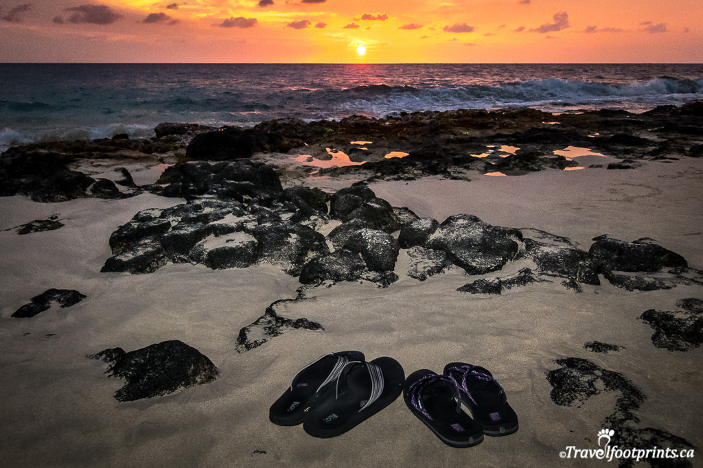 flips flops on the sand with hawaii sunset
