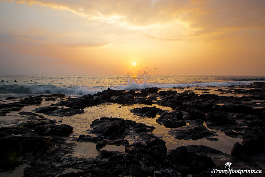 orange hawaii sunset with ocean waves and rocks