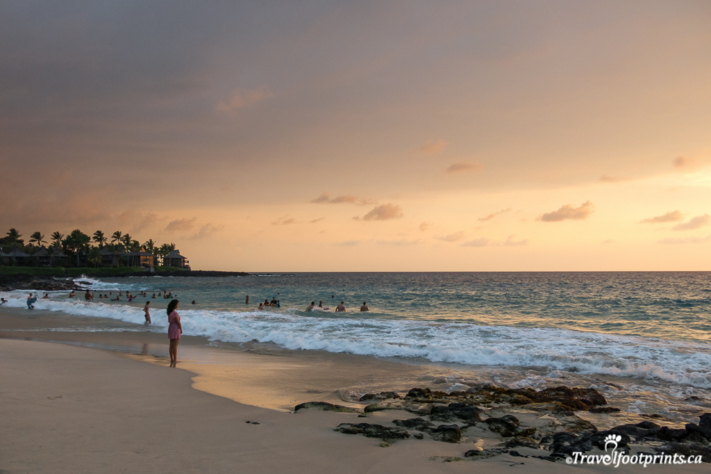people standing on beach watching hawaii sunset