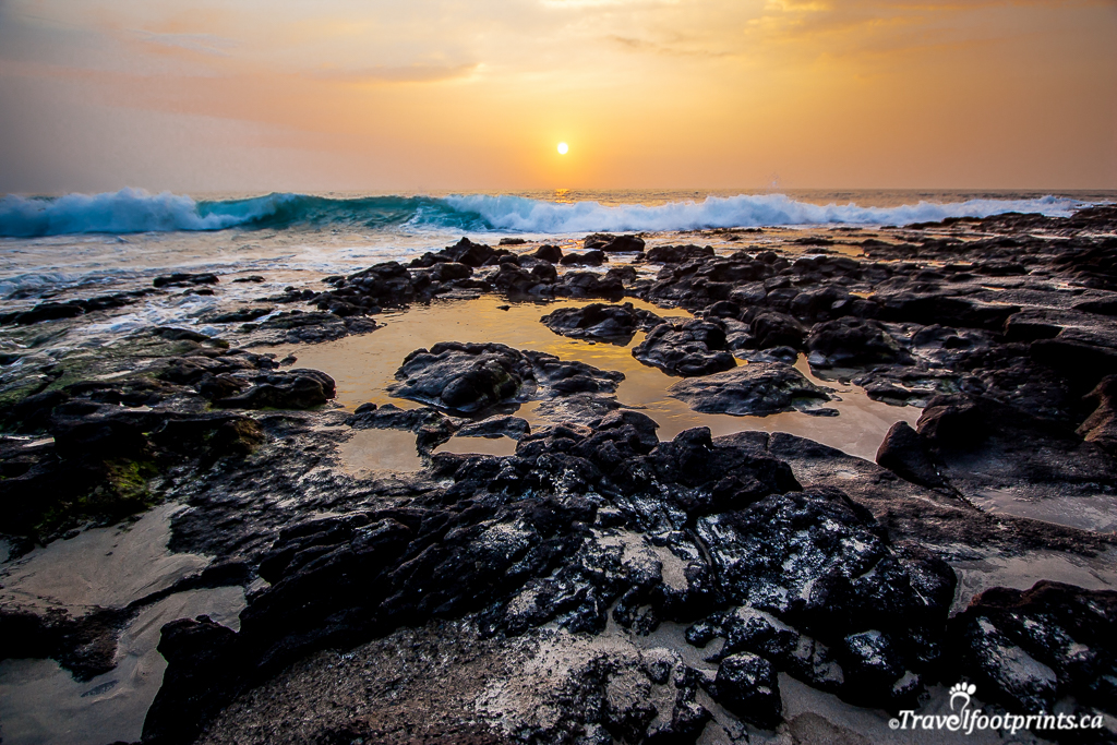 rough beach rocks and ocean waves in hawaii sunset