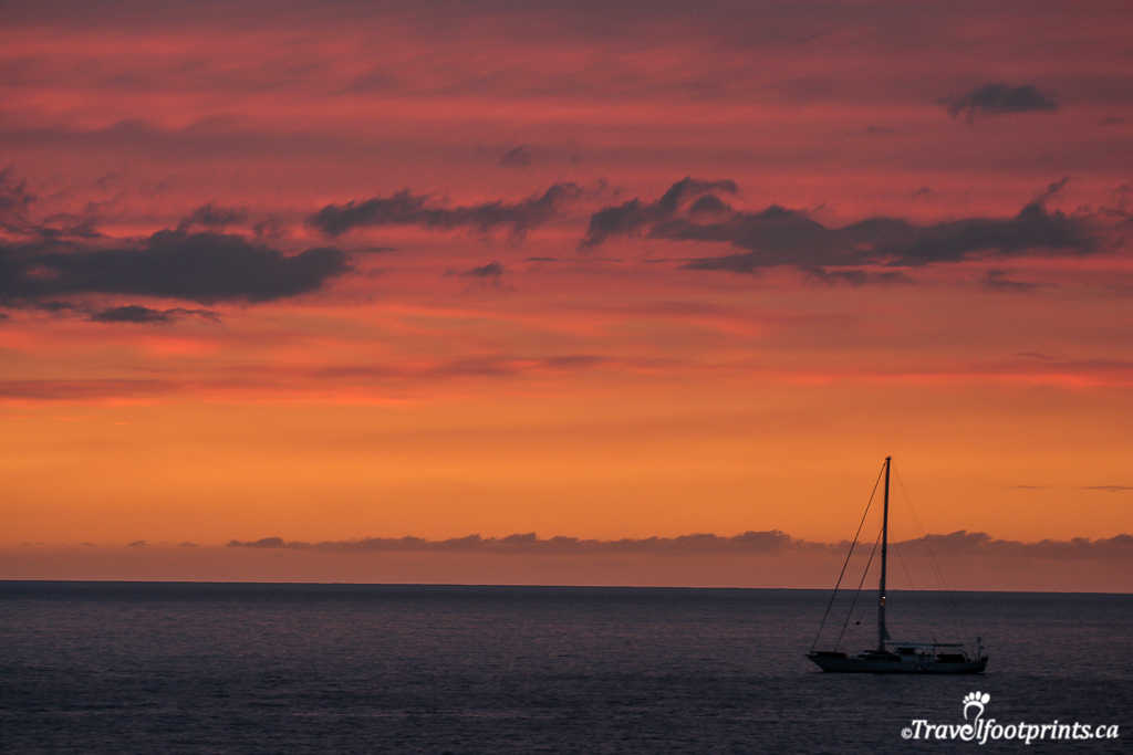 sailboat in orange pink and red sunset