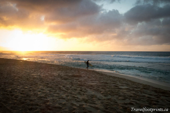 man-with-surfboard-walking-beach-sunet-oahu-hawaii-islands
