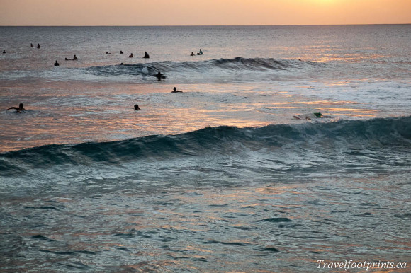 surfers-waiting-for-next-big-wave-end-day-sunset-orange-glow-beach-oahu-hawaii