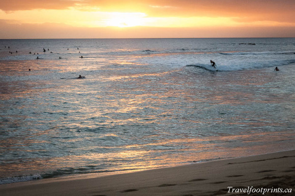 surfers-in-water-with-sunset-in-background-oahu-hawaii-beach