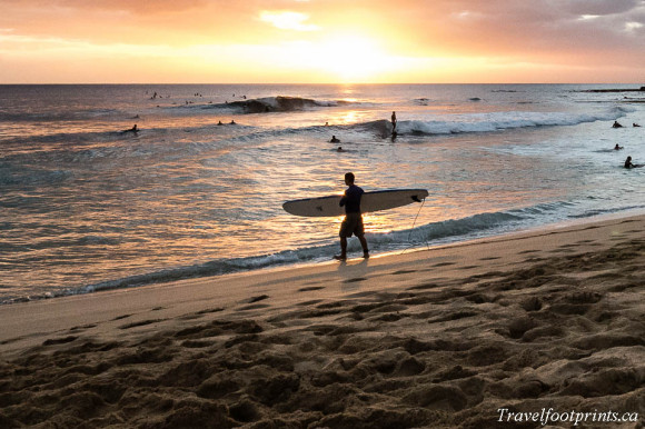 man-walking-with-surf-board-in-sunset-oahu-hawaii-beach